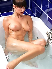 Very cute babe lies in the hot bathtub water