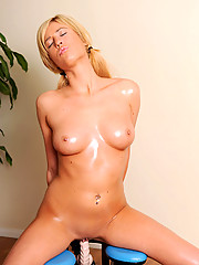 Round titted hottie rides sex machine with her naked body full of oils