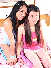 Two sexy latina lesbians undressing on a bed