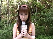 Kinky Nana toys a microphone outside while guy watches