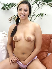 A horny latina masturbates alone on the couch