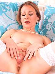 Brunette milf Tiffany slides off her sexy panty and pinches her big tits on the bed