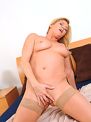 Anilos cougar strips on her bed and starts fucking her pussy with her talented fingers