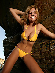 Alex on the rocks in a yellow bikini