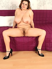 This chubby older women loves getting freaky. Watch in amazement as she slides out of her back lingerie and gapes her moist pussy on the couch.