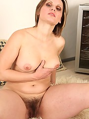 Sexy mature lady Saxana gets frisky on the soft floor of her living room. She hopes no one catches her but she plays with her hairy pussy anyway.