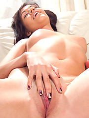 Lovely Jenica doing solo teasing on the sofa with her hands busy stroking her juicy assets
