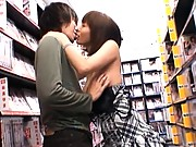 Yuma Asami shows her tits to a young guy at an adult video store