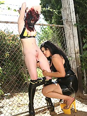 Sexy redhead wearing a gas mask tied to fence