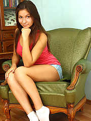 Cute teen Ania exposes her hot ass on the chair and gives a seductive look