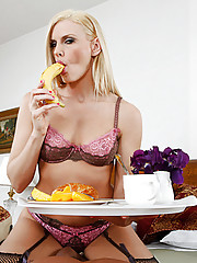 Darryl Hanah is starting the day out right by making breakfast in bed.  She playfully puts a banana in her mouth and all of a sudden she