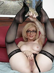 Nina Hartley posing on the bed in black stockings