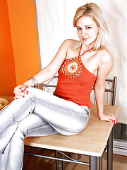Anilos Laurita in tight jeans and a sexy top shows off her body on the tabletop