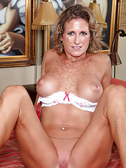 Sexy mature lady flirtatiously shows off her big tits as she slips off her lingerie