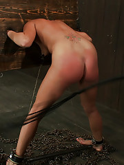 Cute redhead Charlie Ann bent over in wooden stocks, her pink ass hit with every nasty sensation we can think of.
