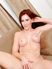 Horny redhead Catherine Desade fucks her pussy using a magic wand on the couch