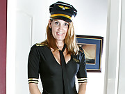 Enticing cougar takes off her pilot costume and shows her pussy