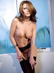 Lexi Stone sits by the window and massages her wet pussy.