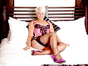 Short blonde haired milf massages her stocking clad legs in bed