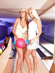 Two pretty teenage girls bowling and kissing
