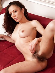 Natural nympho Laura B lays her bare body down on the sofa and teases her thick dark pussy hair with her fingers. The matted hair tufts begin to stand up on their own.