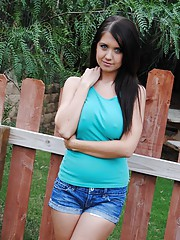 Cute brunette strips in her garden