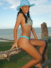 Karla Spices hangs out by the shore wearing bikini bottoms and a blue hat