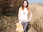 Teen masturbates in a large field outdoors