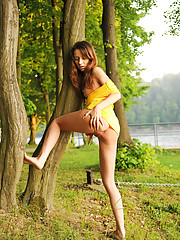 Daring Nubile Inna Blossom lifts her dress exposing her bare pussy outdoors