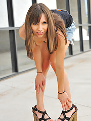 Risi in a skirt and heels flashing outdoors