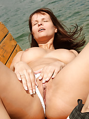 A cutie undressing on a small boat outdoors
