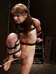 Petite brunette bound tight, caned hard. Her feet and neck strained. She struggles to keep balance, enduring orgasm denial being vibed and fingered.