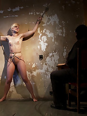 Tall long legged blond is held in a creepy room by masked man. She