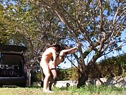 Shou Nishino Asian is pumped from behind holding a tree in a park