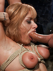 Hot blonde gets ass fucked in bondage in front of a large crowd
