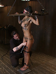 Bonnie is contorted into a standing metal strappado, challenging back arch, and then standing on the spiky board in stocks and tormented by clever JP.