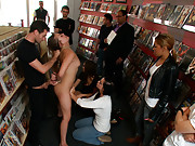 19 year old gets fucked in the ass in a comic book store while people grope her. Then she is fucked by lesbian couple with a giant strap-on cock!