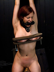 Redhead with big tits, bound in extreme metal bondage. Pussy takes a beating, tits get brutalized. She is made to cum with violent machine fucking.