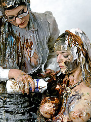 Sweethearts playing with large bottles of mud