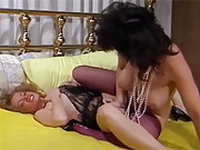 Two horny retro babes scissoring in a big bed