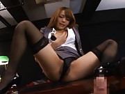Rio Asain in office suit sits with legs open on desk rubbing cunt