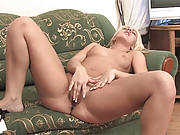 Blonde on a couch caressing her drenched clit