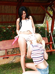 Lesbian beauties massaging wet cunts outdoors