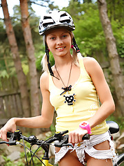 Blond and blue-eyed teen Pinky June gets naked while riding bike