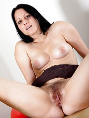 Hairy woman Amber Lustful gets naked in playroom