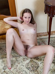 Hairy girl Flora strips naked in her hallway