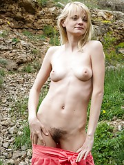 Petite Kira S plays with her hairy pussy outdoors