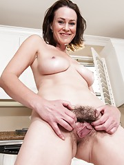 Hairy woman Veronica Snow strips in the kitchen