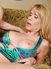 Busty cougar Desiree Dalton has sex with younger cock and rides it on the couch.