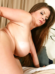 Busty milf June Summers fucks younger cock and loves riding it on the bed.